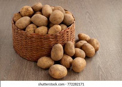 A lot of potatoes in a wicker box. Potato tubers on a wooden background. Potatoes in a wicker basket and next to a basket. Harvest of potatoes. Many vegetables are harvested in a box.