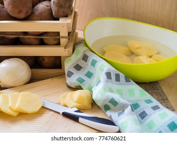 potatoes in wooden box peeled potatoes in a water and sliced potatoes on cutting board with towel and knife. making dinner concept
