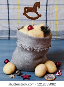 Potatoes with a wooden hobbyhorse in a bag standing on a blue surface, three potatoes, Christmas-tree decorations, two stars,a strobile,a candy cane, a stick of a Christmas tree & a slice of an orange