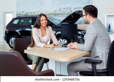 Potential female vehicle buyer carefully listening to car dealer you car that are in salon.