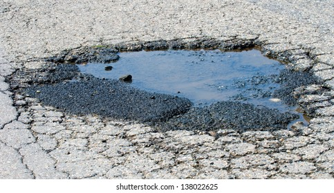 Pothole in the asphalt filled with water