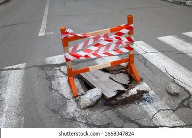 Pothole auf der Fußgängerüberquerung auf der Straße. Hölzerne Sicherheitsbarriere mit Sicherheitsstreifen über dem Pothol.