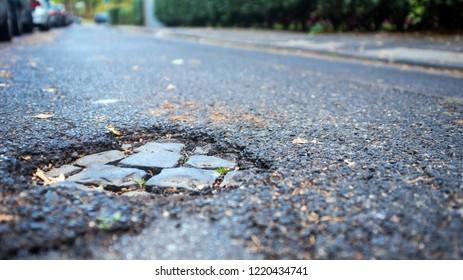pothole on small street, green bushes aside