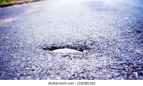 pothole on a street, light coming in from top