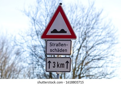 "Pothole sign warning car driver at road damages german text translation ""road damaged"""