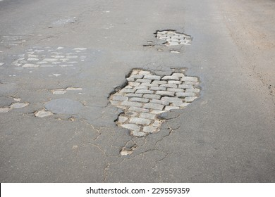Potholes in an asphalted road let exposed the antique paving in Rosario city, Argentina