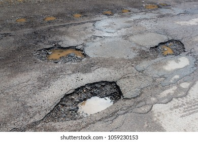 Potholes on a paved road. The road is in very poor condition. There is dirty water in the potholes.