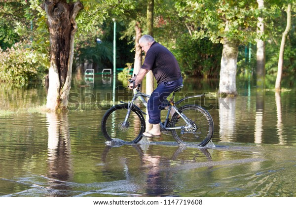 Poti town, Georgia. 2th august of 2018. A man riding a bicycle through a flooded street. Aftermath of a thunderstorm.