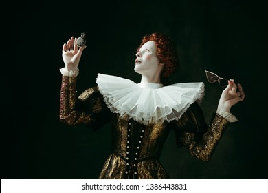 Potion. Medieval redhead young woman in golden vintage clothing as a duchess in red sunglasses holding a parfume on dark green background. Concept of comparison of eras, modernity and renaissance.