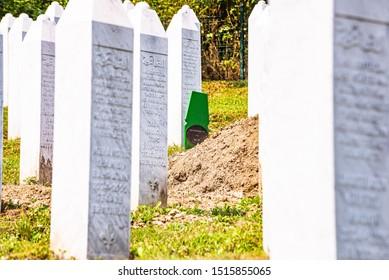 Potocari, Bosnia and Herzegovina - July 31, 2019. Green grave of last DNA identified victim of Srebrenica massacre between white tombstones