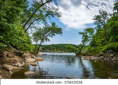 Potomac River running through a forest in Great Falls Park with blue skies overhead during summer