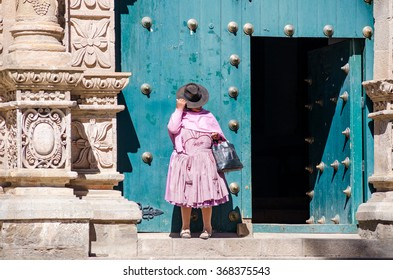Potosi, Bolivia - circa May 2015 - Unidentified woman walks out of the Potosi City Cathedral.