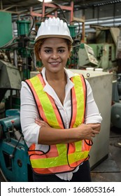 potrait mixed race female engineer working in factory area.