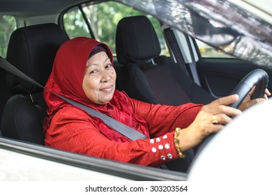 potrait of muslim woman driving her car