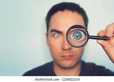 Potrait of young man looking through magnifying glass on white blurred background. View to male blue eye through the lens. Loupe with macro eye in person's hand on the foreground. Information search