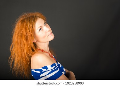Potrait of young woman with red curly hair on black background