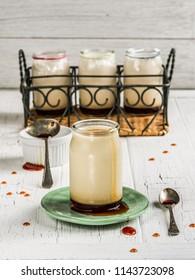 Pots of caramel yogurt on a white table board