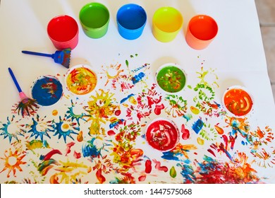 Pots with colorful dye used for fingerpainting. Creative art for kids