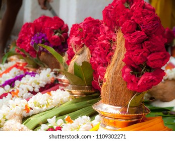 Pots decorated with garlands, leaves and coconuts in a ritual at a Hindu temple.
