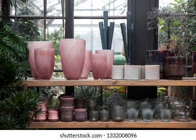 Pots and glass vases on display in a garden center.