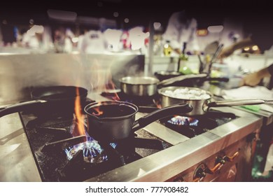 Pots and pans on stove in restaurant kitchen, chef working in the background