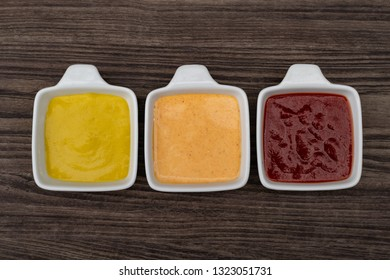 """""""Pots with sauces (mustard, katchup, marie rose sauce ) arranged on rustic wood background. With writing area."""""""