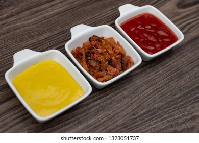 """""""Pots with sauces (mustard, katchup, marie rose sauce and bacon) arranged on rustic wood background. With writing area."""""""
