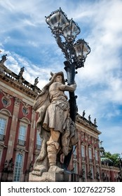 Potsdam, Germany - May 16, 2012: Sculpture of Torchbearer, dressed as a germanic tribe warrior in front of the main entrance to the New Palace