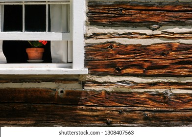Potted flower in open window of historic log cabin with aged red wood and mortar