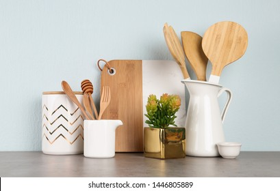 Potted plant and set of kitchenware on grey table near light wall. Modern interior design