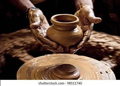 A potter first sculpts the pot, then in a single motion cuts it off the base using a thread, scoops the pot up and places it by the side.