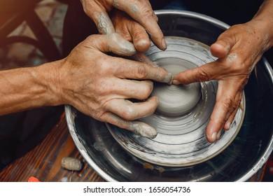 Potter make a small jug. Hands of a potter at work