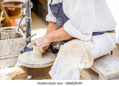The potter man making clay jugs outdoors