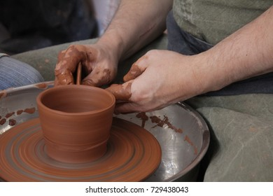 The potter is molding from clay on a potter's wheel. The hands of the potter