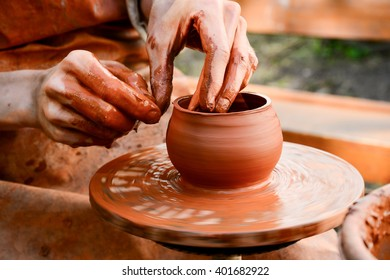 the Potter molds a pot from clay on a Potter's wheel