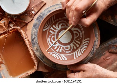 A potter paints a clay plate in a white in the workshop, top view, close-up, selective focus.