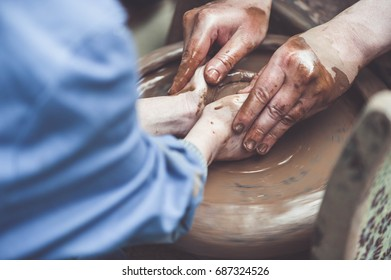 Potter teaching a girl to make clay pot on potter's wheel. Close-up of hands