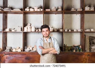 potter, tools, ceramics art concept - a handsome young brunette with a beard dressed in an apron, smiling male master ceramist at workplace with finished jugs and cups background