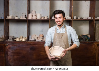 potter, tools, ceramics art concept - happy handsome young brunette male dressed in an apron, master standing with finished utensils, smiling ceramist at workplace with cups and jugs at background