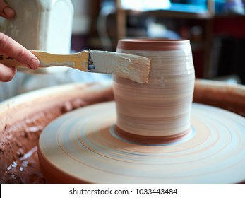 potter at work. production process of pottery. Application of glaze brush on ceramic ware.