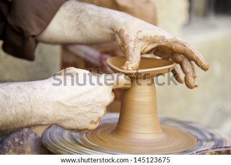 Potter working with clay, detail of a craftsman working in the city