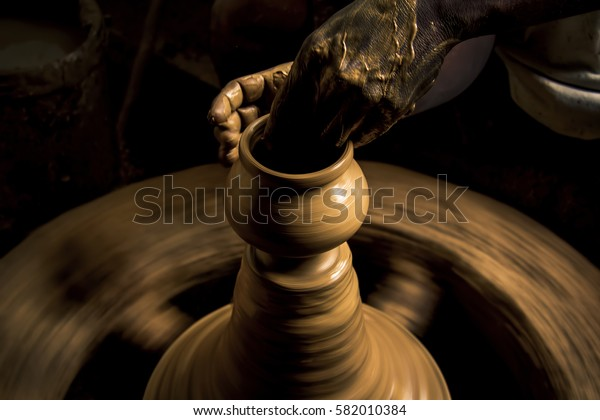A potter works on creating a clay pot at his potters-wheel