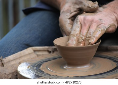 potter's hands creating a new ceramic  of clay on the wheel in the pottery, closeup with selected focus and narrow depth of field