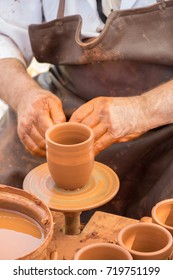 Potter`s hands shaping up the clay of the pot