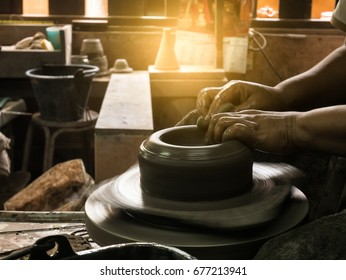 potter's hands shaping soft clay to make an earthen pot