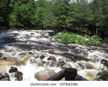 Pottersville, NY / USA - June  1, 2019: A fast-flowing creekbed with large rocks in the Adirondack Mountain forest.