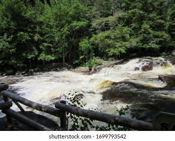 Pottersville, NY / USA - June  1, 2019:  Rapidly moving stream flowing over rocks with wooden fence in foreground.