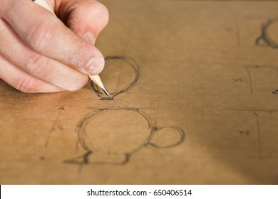 pottery, artisan tools, ceramics art concept - man's hand with pencil, working drawing of planned earthenware, master draws design and fixes sizes of future products, fingers in the clay