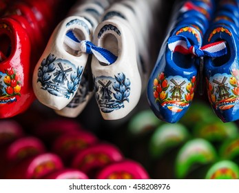 Pottery Clog shoes has red rose inside hang on black wall in Amsterdam , Netherlands , Traditional souvenir