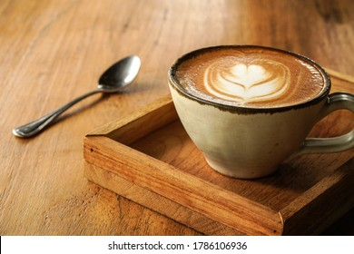 pottery cup of coffee with latte art for hot cappuccino in wooden tray on the table
